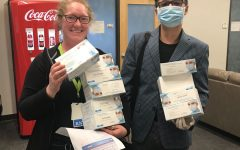 Liu poses with a smiling health worker, holding boxes of donated masks.