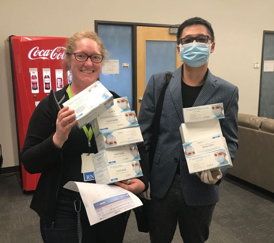 Liu+poses+with+a+smiling+health+worker%2C+holding+boxes+of+donated+masks.