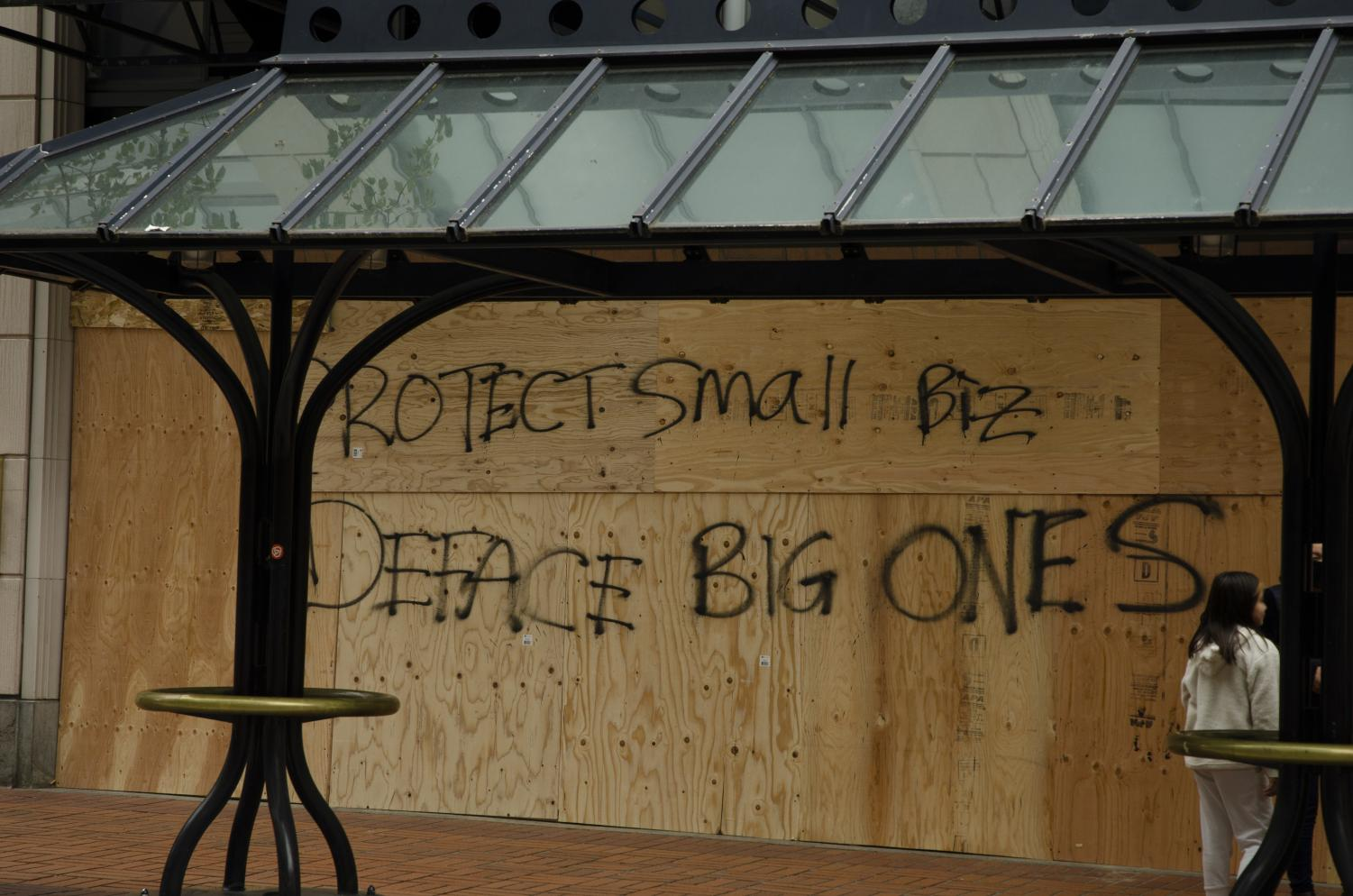 """Graffiti in front of the boarded up Louis Vuitton building reads """"Protect small biz, Deface big one."""""""